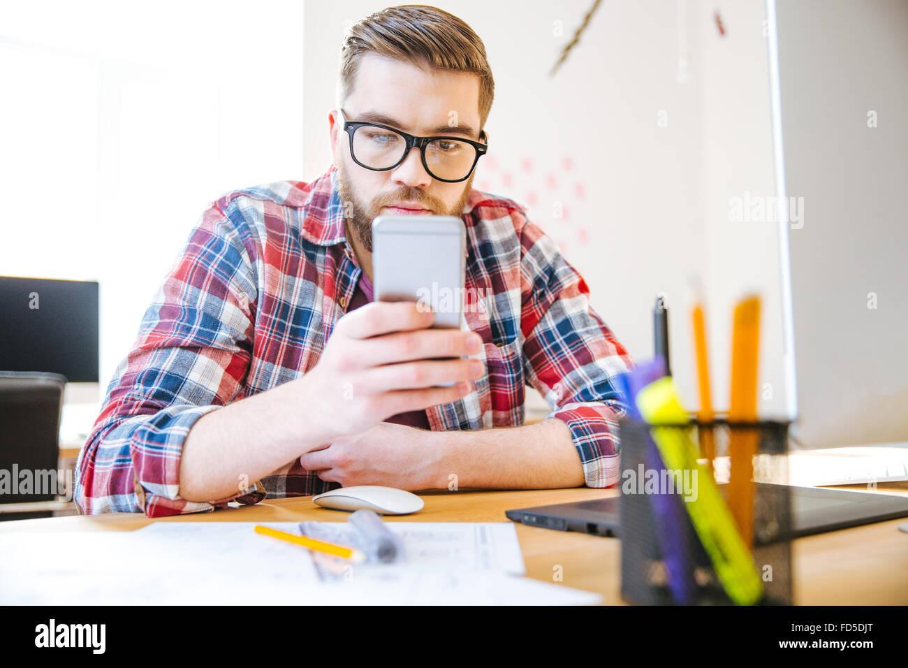 Hübscher konzentrierte junger Mann mit Bart im karierten Hemd am Tisch sitzen und mit Handy Stockbild
