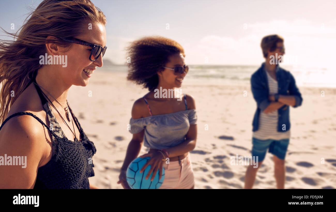 Lächelnde junge Frau und Freunden am Strand mit Volleyball spielen. Junge Menschen, Sommerurlaub am Strand Stockbild