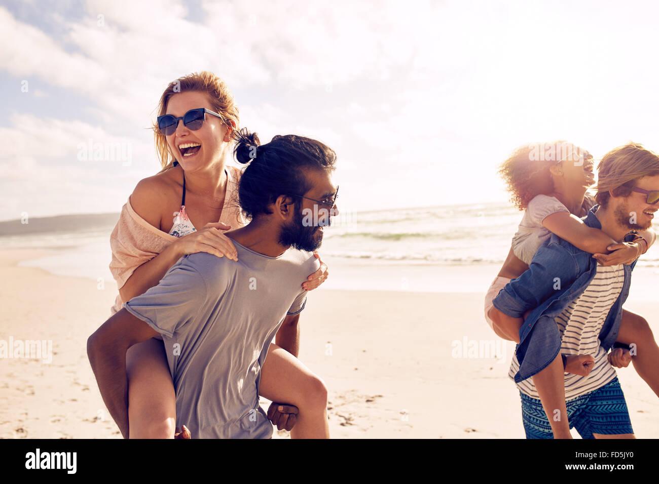 Glückliche junge Männer geben Huckepack Fahrt für Frauen am Strand. Heterogene Gruppe von jungen Stockbild