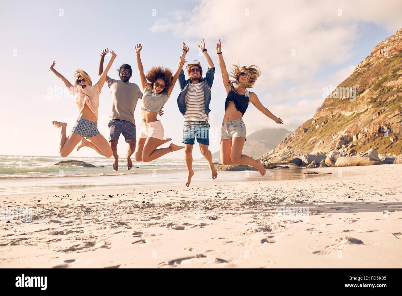 Gruppe von Freunden zusammen am Strand Spaß haben. Glückliche junge Menschen springen am Strand. Gruppe Stockbild