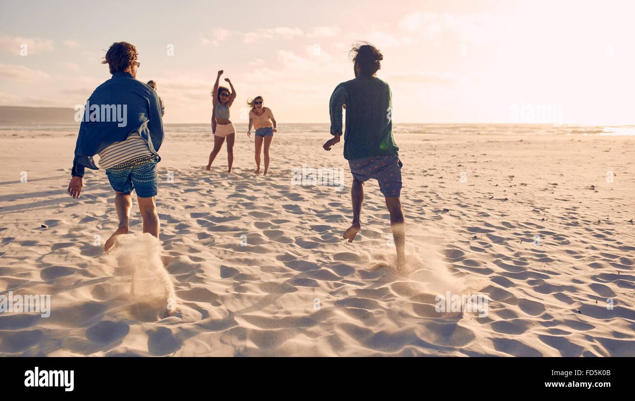 Gruppe von Jugendlichen ausgeführt und im Wettbewerb zusammen an einem Sandstrand. Junge Männer, die ein Stockbild