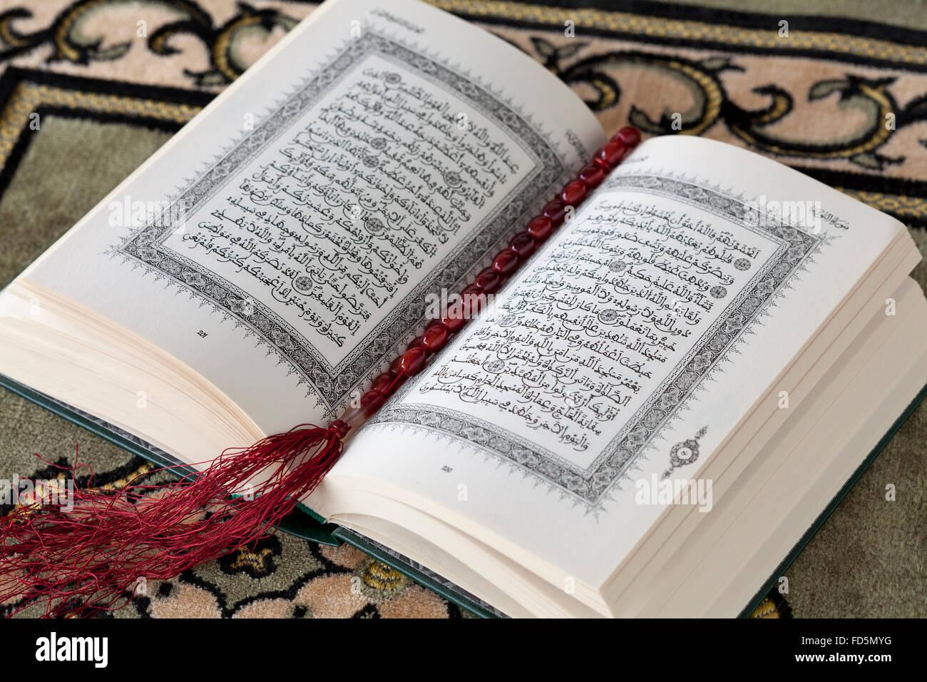 Aufgeschlagene Buch der Koran und die Gebetskette auf einem Teppich Stockbild