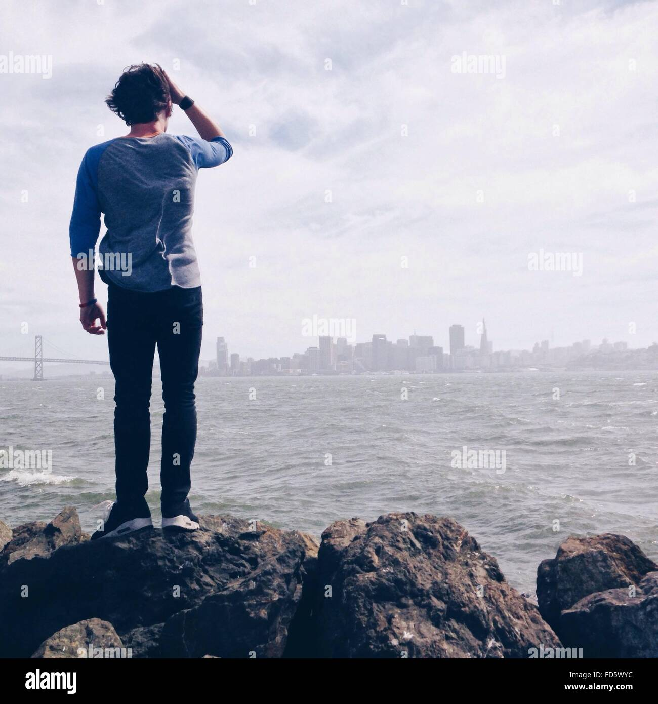 Mann auf Felsen Blick auf fernen Stadt Stockbild