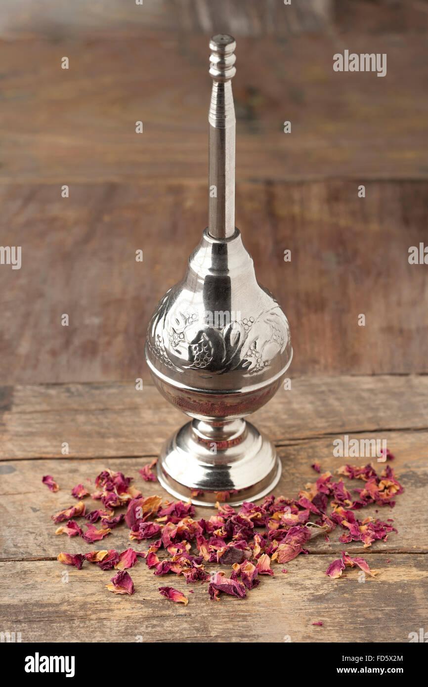 Marokkanische Rose Wasser Sprinkler und Blütenblätter auf Holztisch Stockbild