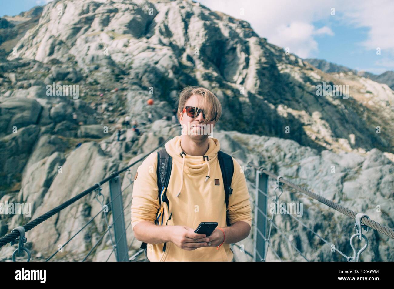 Junger Mann mit Smartphone auf hängende Brücke Stockbild