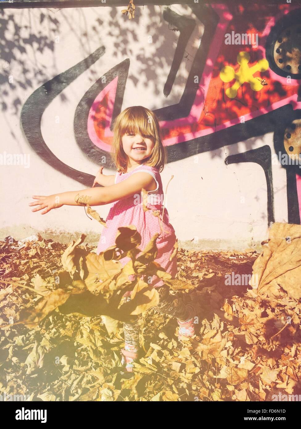 Niedliche Mädchen spielen mit trockenen Blättern gegen Wand Stockbild