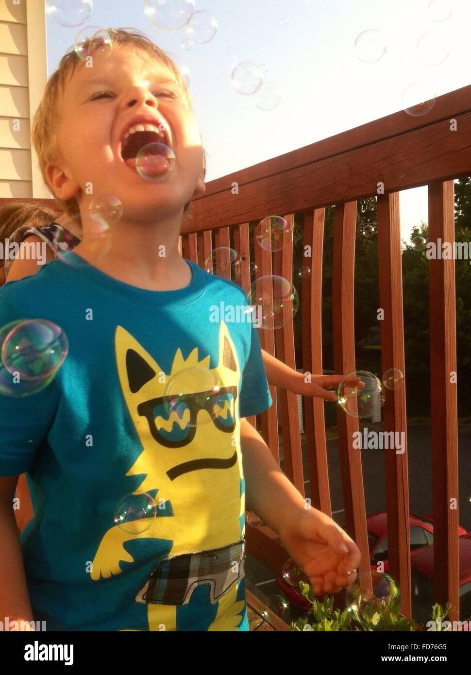 Jungen spielen mit Luftblasen auf Balkon Stockbild