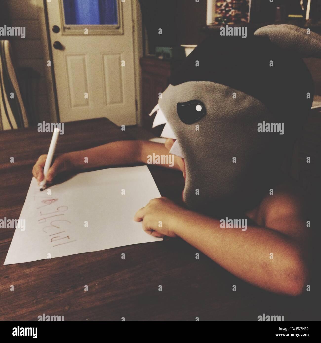 Junge schreiben während des Tragens Maske zu Hause Stockbild