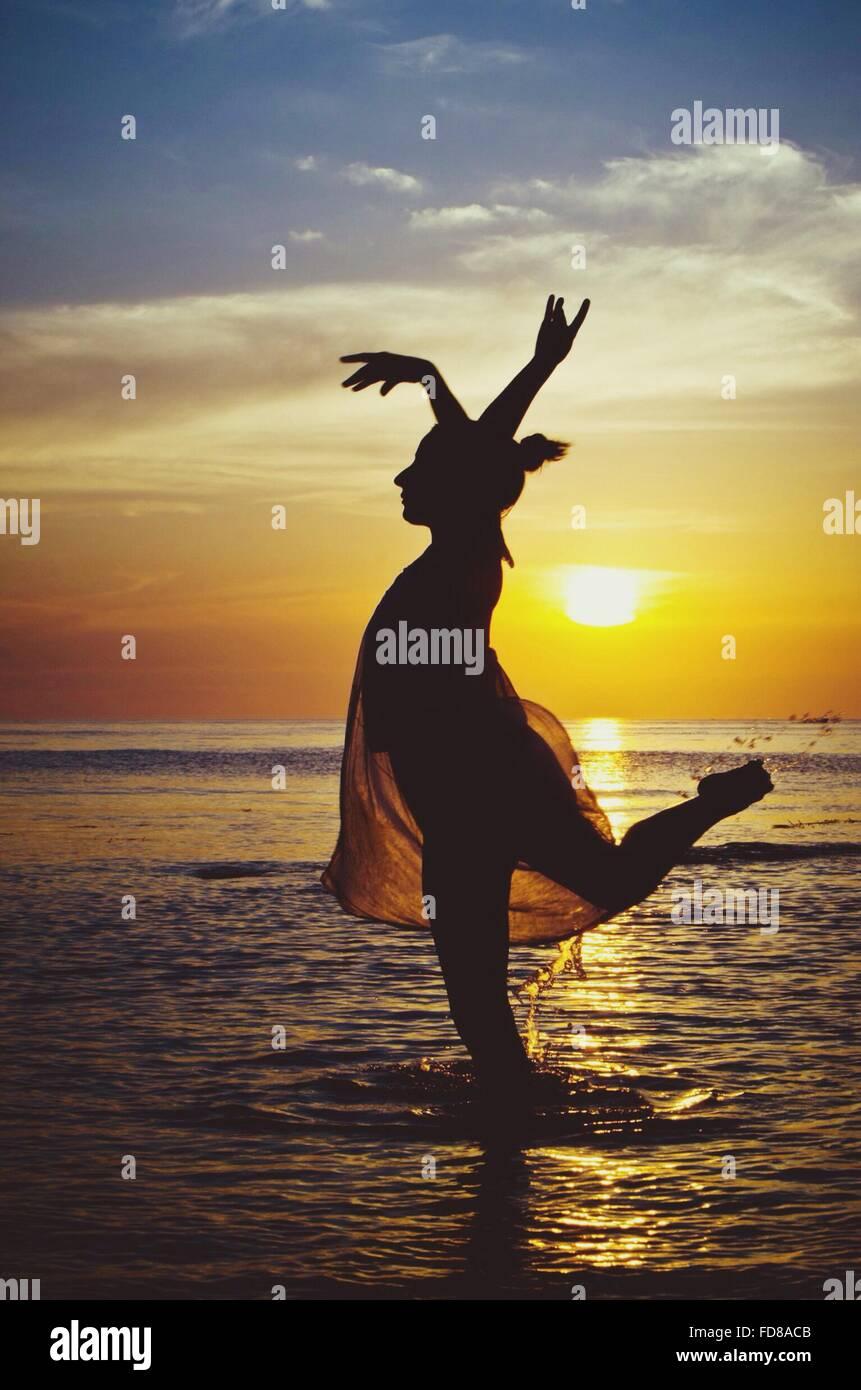 Seitenansicht der Silhouette Frau stehen auf einem Bein am Strand Stockbild