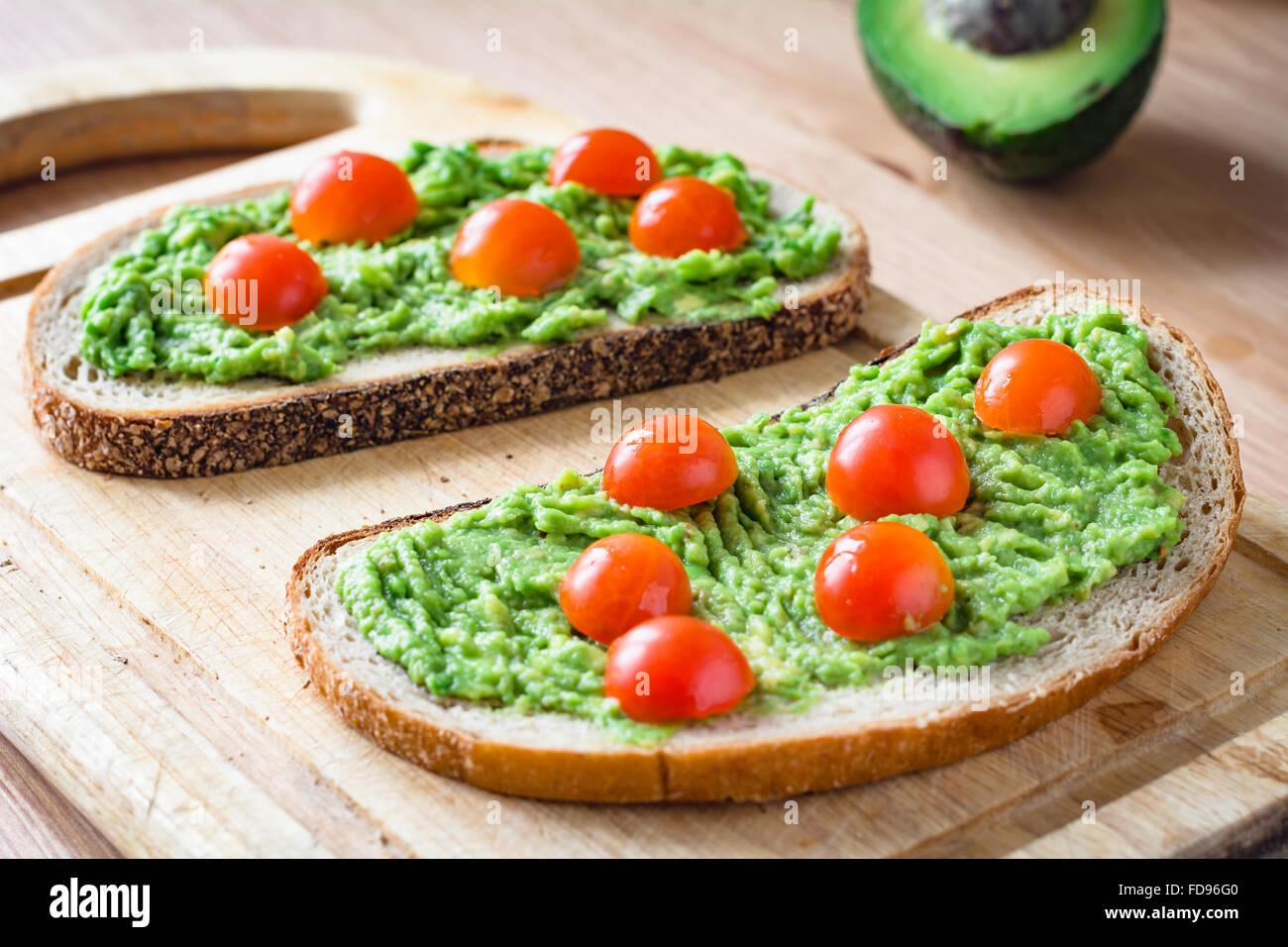 guacamole und brot toast mit avocado und cherry tomaten auf holzbrett stockfoto bild 94245088. Black Bedroom Furniture Sets. Home Design Ideas