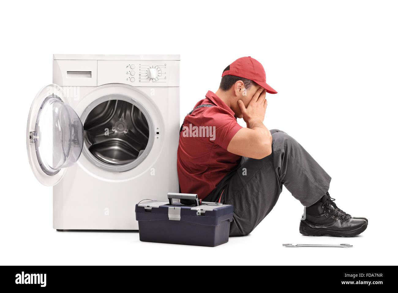 Studioaufnahme von einem enttäuscht junge Handwerker sitzen durch eine kaputte Waschmaschine isoliert auf weißem Hintergrund Stockfoto