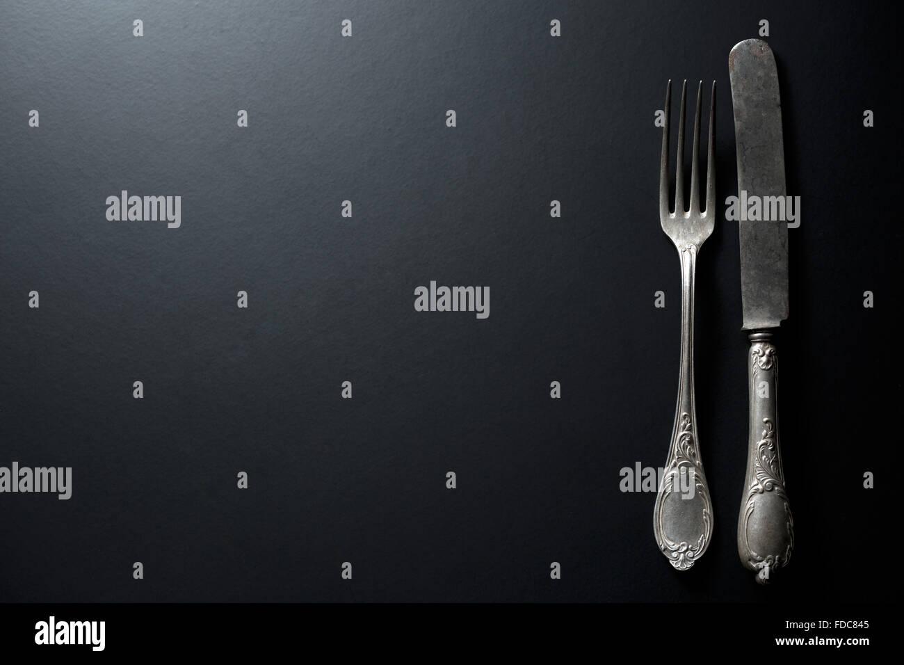 alte Vintage Messer und Gabel auf schwarzem Hintergrund Stockbild