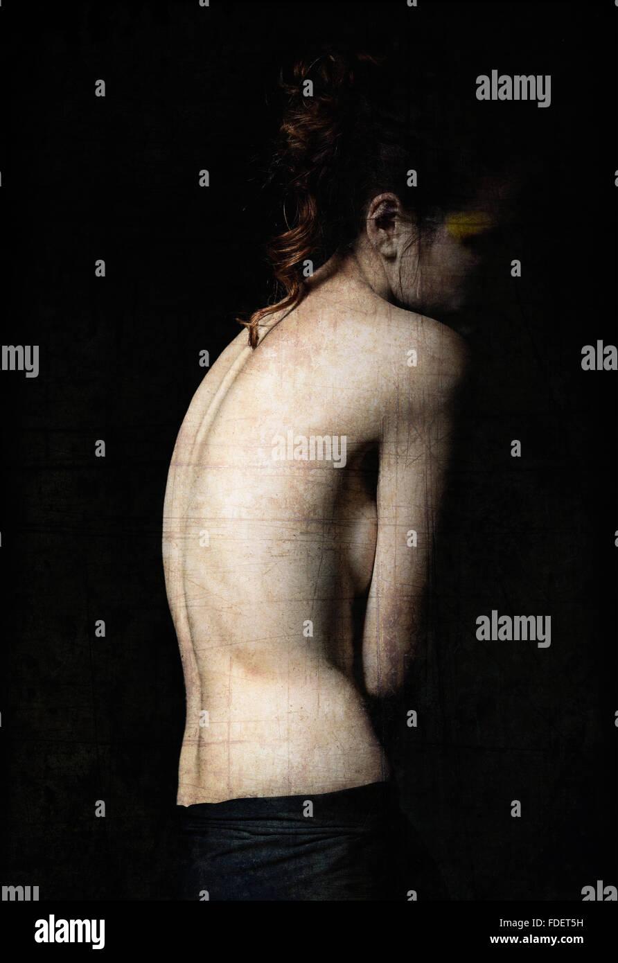 Düsteres Porträt einer jungen Frau unter der Dunkelheit. Grunge-Textur-Effekt Stockbild