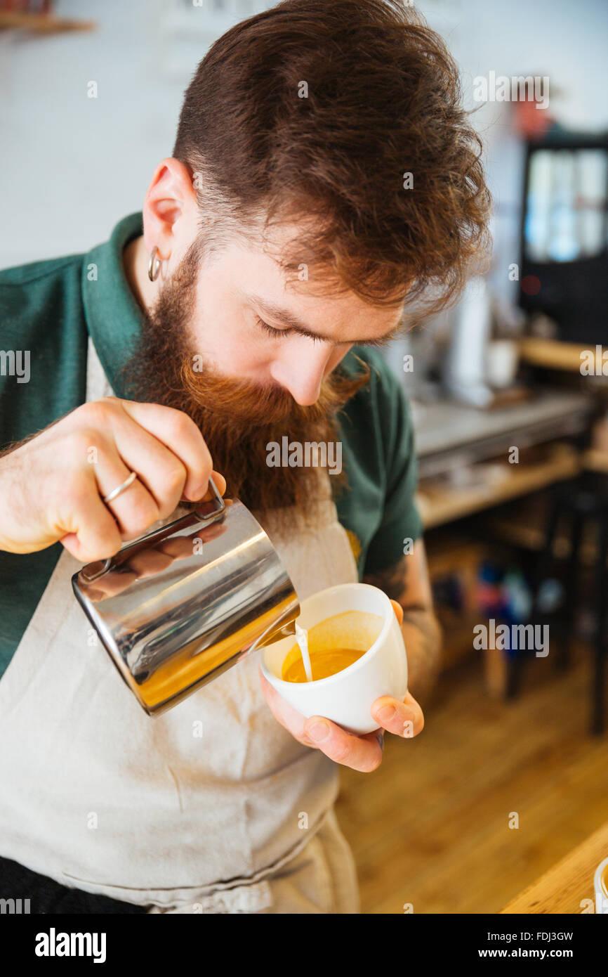 Barista gießt Milch in Tasse Kaffee in der Cafeteria Stockfoto