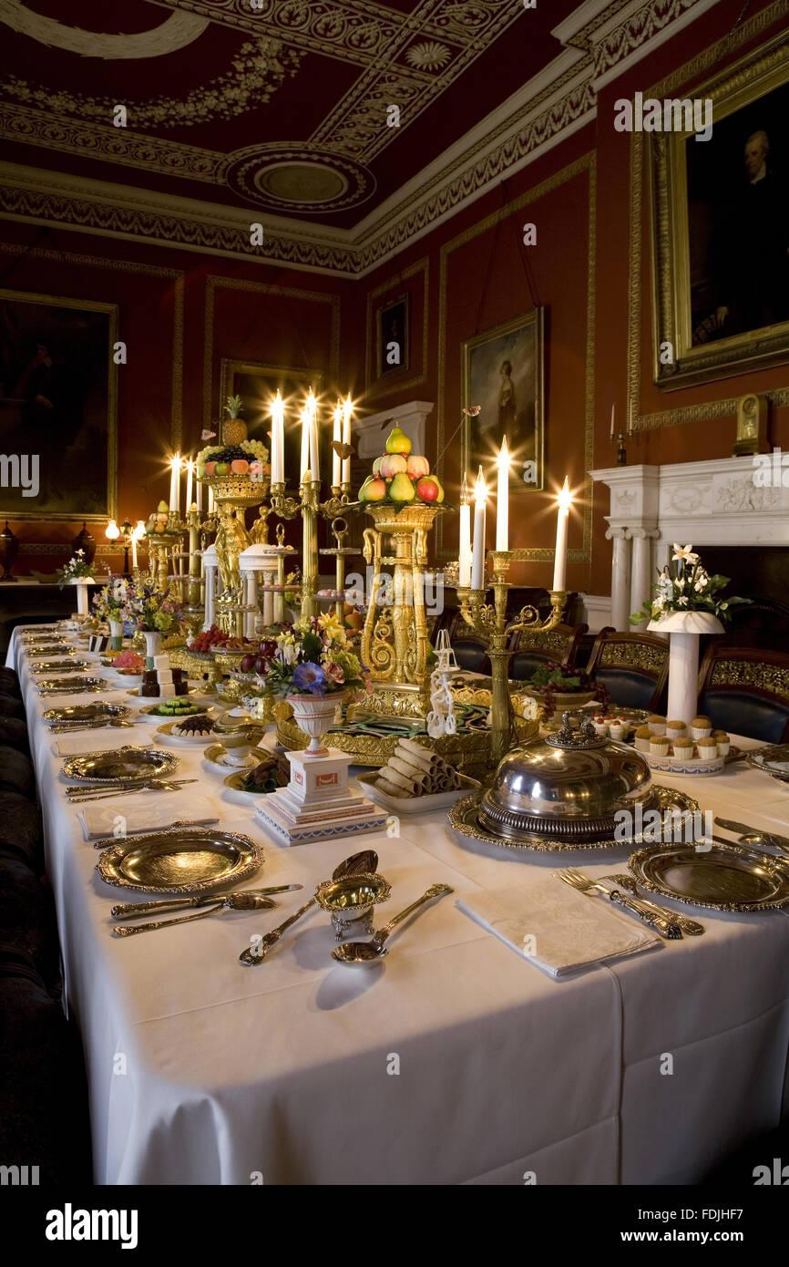 Der Speisesaal im Attingham Park, Shrewsbury, Shropshire, mit dem Esstisch gelegt für ein Galadiner und mit Tischdekorationen und Kandelaber. Stockfoto