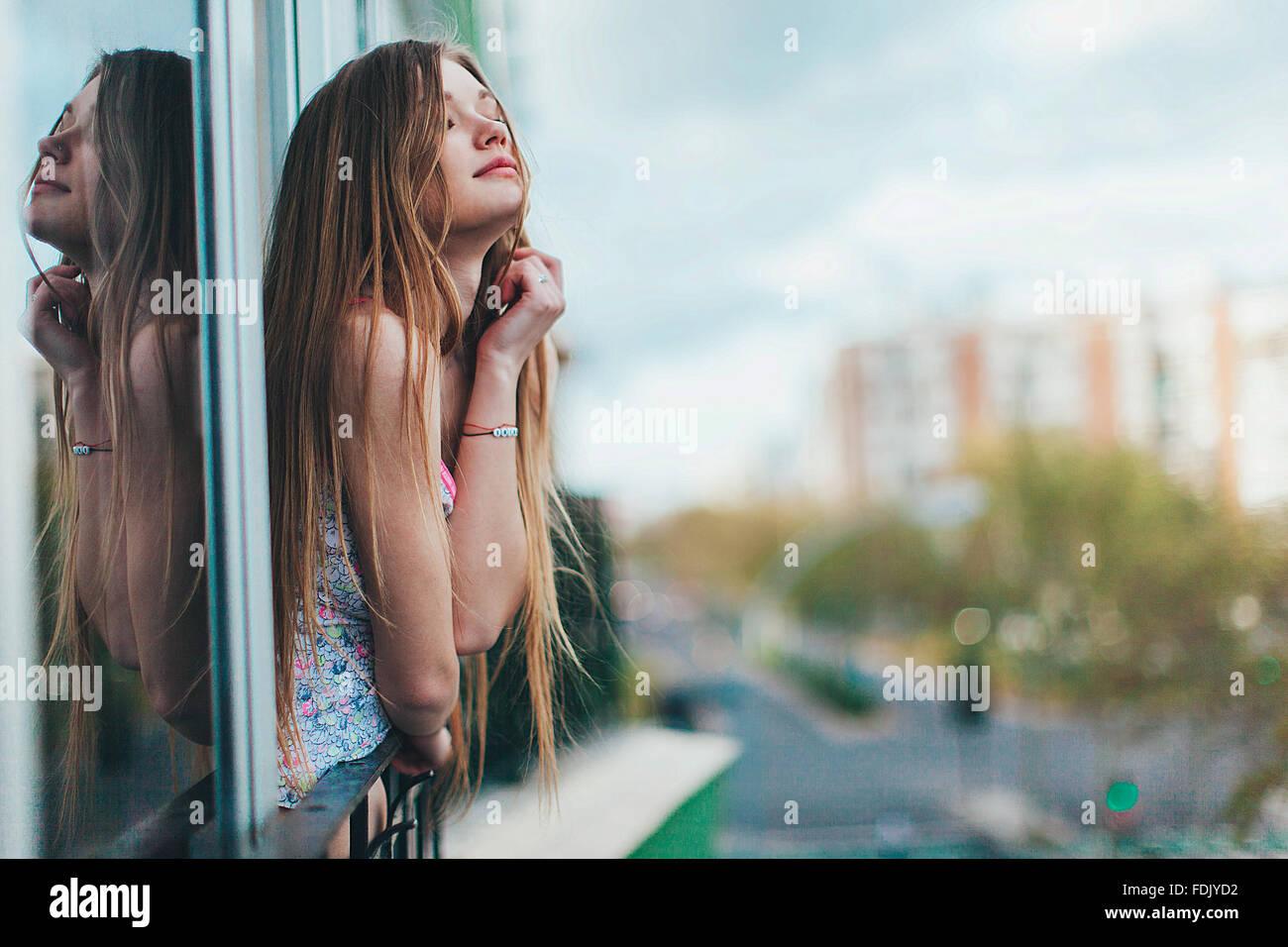 Junge Frau lehnt sich aus dem Fenster in der Stadt, Sevilla, Spanien Stockbild