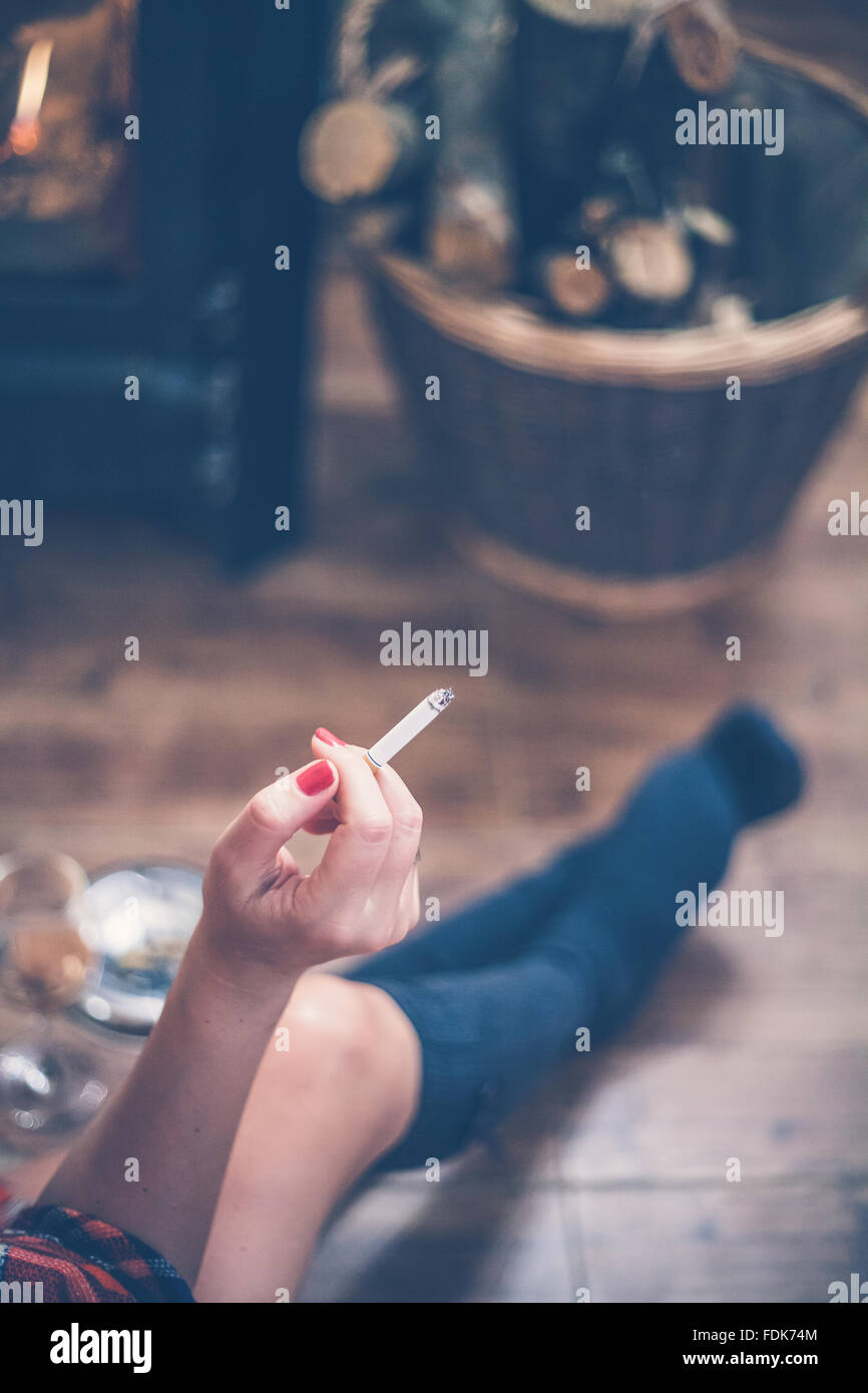 Frau sitzt vor Holzofen, eine Zigarette rauchend Stockbild