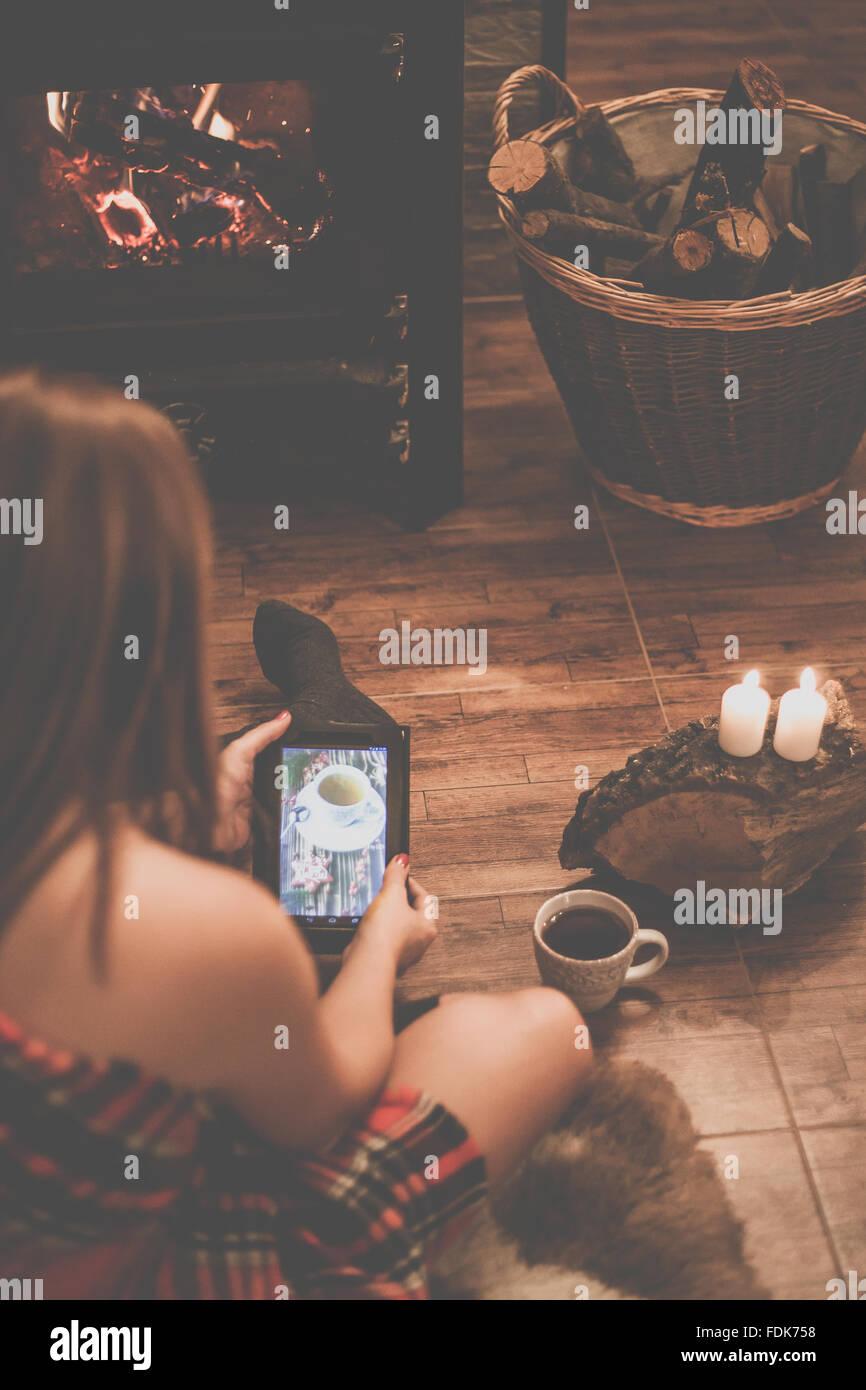 Frau sitzt vor einem Holzofen mit einem digital-Tablette Stockfoto