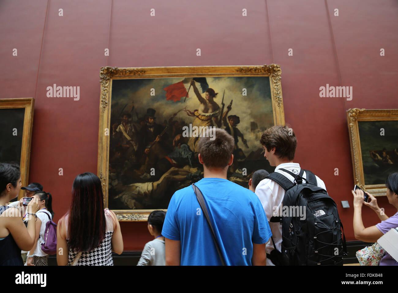Tourist im Louvre-Museum.  Freiheit führt das Volk, 1831. Von Eugene Delacroix. Paris. Stockbild