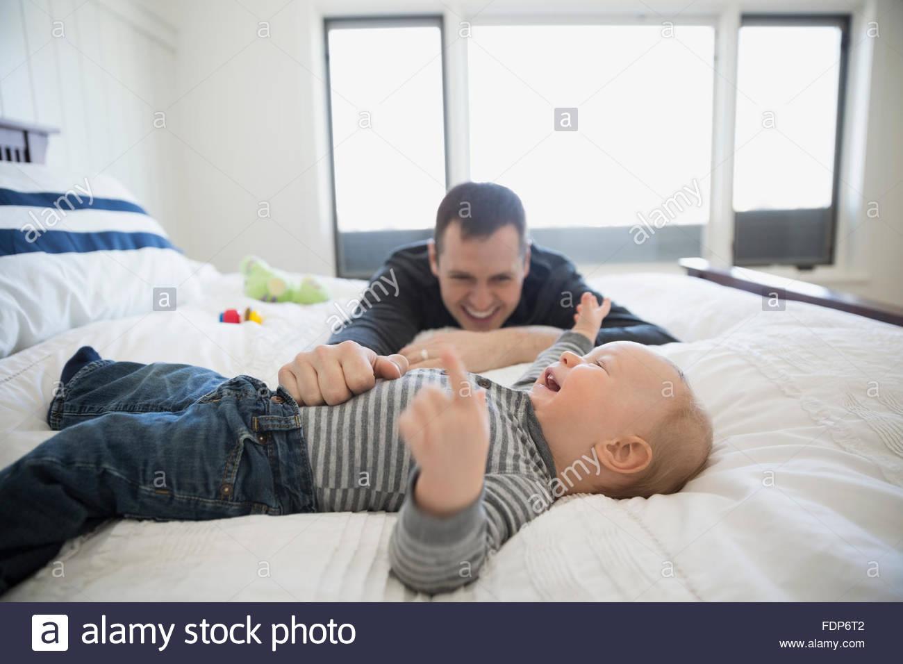 Vater und Baby Sohn lachend auf Bett Stockbild