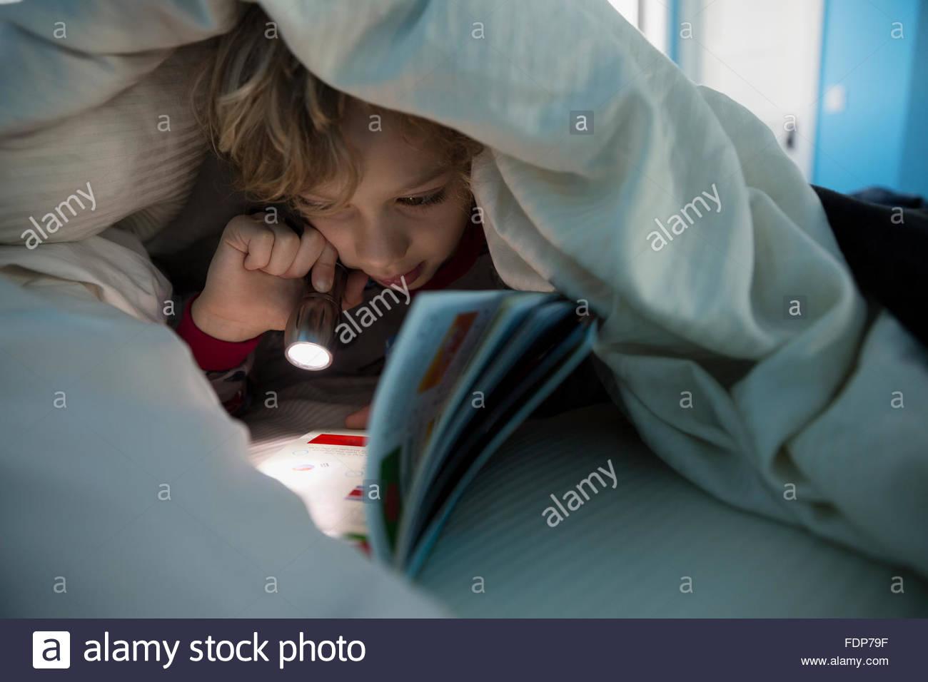 Junge liest Buch mit Taschenlampe unter der Bettdecke Stockbild