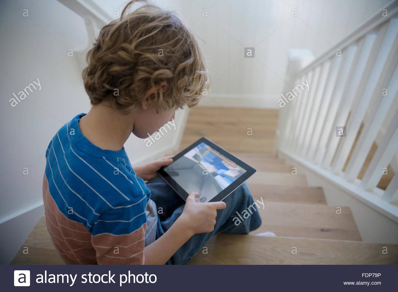 Junge mit digitalen Tablet sitzt auf der Treppe Stockbild