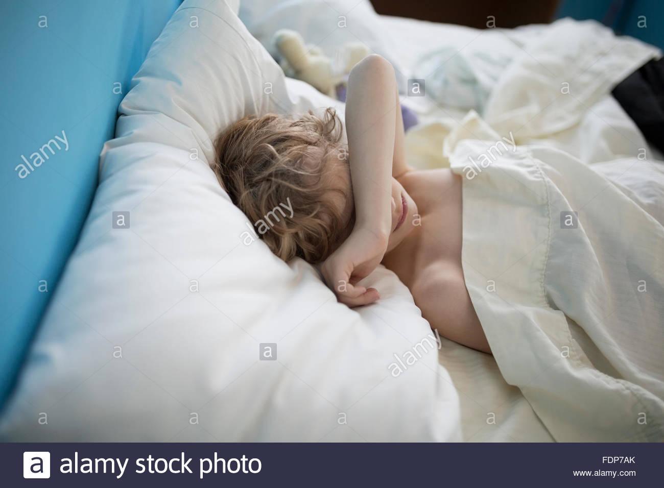Müde Jungen schlafen mit Arm über Augen Stockbild