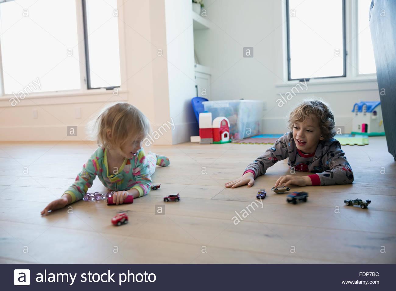 Bruder und Schwester spielt mit Spielzeug-Autos-Boden Stockbild