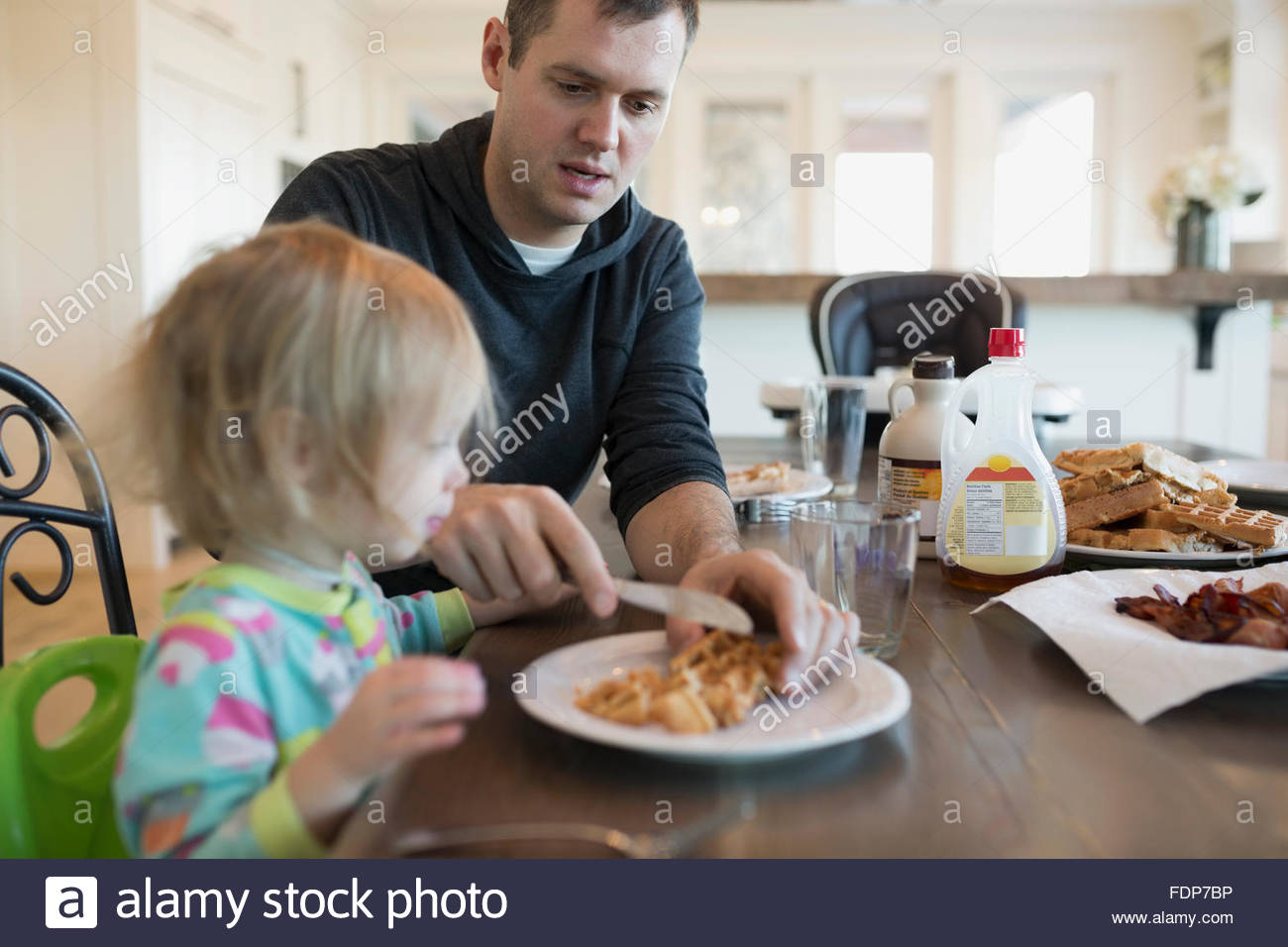 Vater schneiden Waffeln für Tochter am Frühstückstisch Stockbild