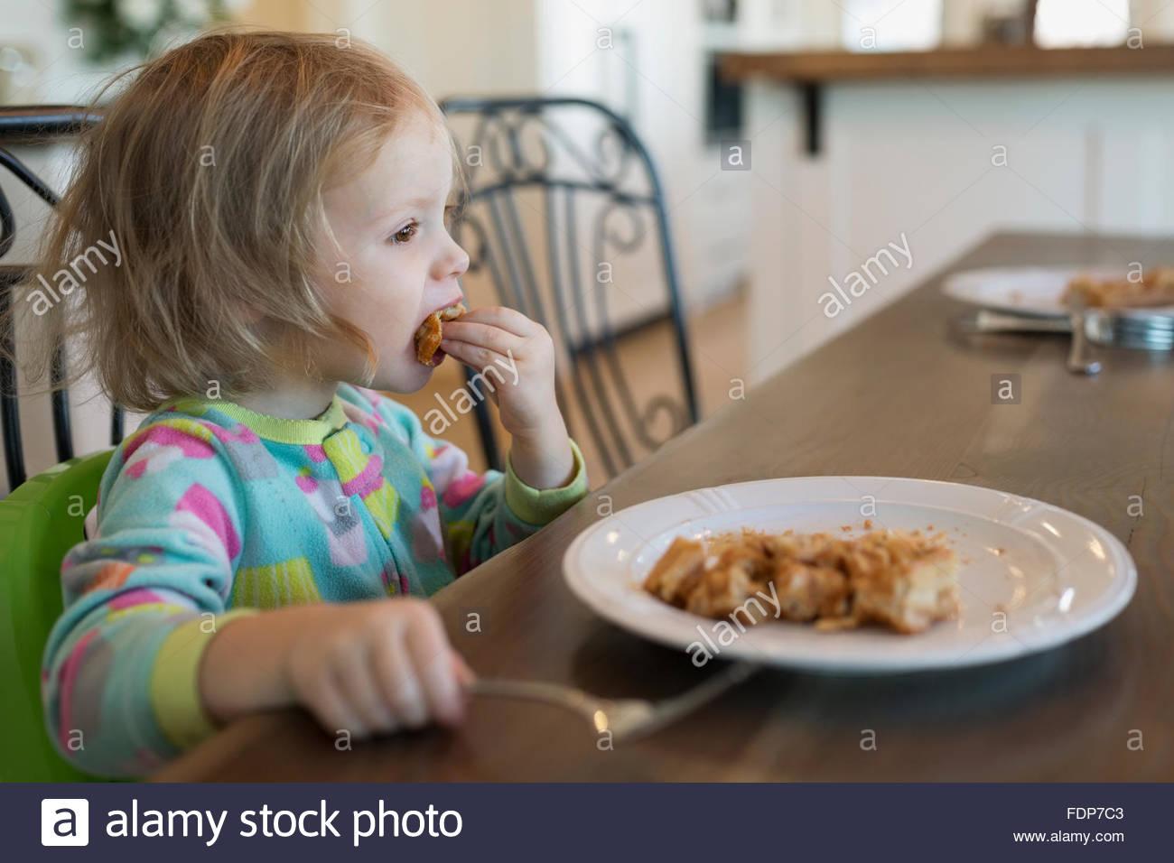 Mädchen essen Waffeln am Frühstückstisch Stockbild