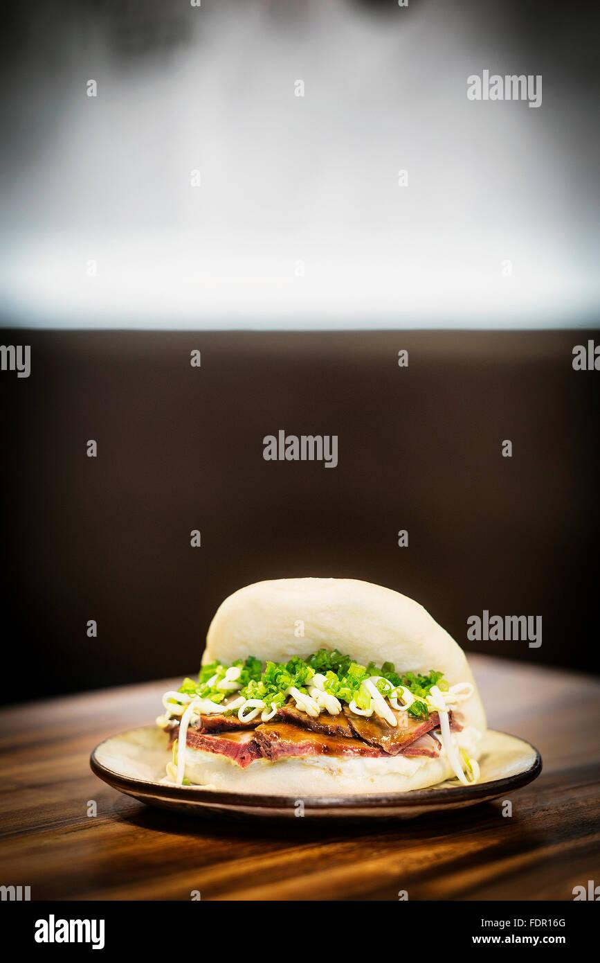 Gebratenes Schweinefleisch Soja Bohnen und Schnittlauch moderne asiatisch trendige sandwich Stockbild