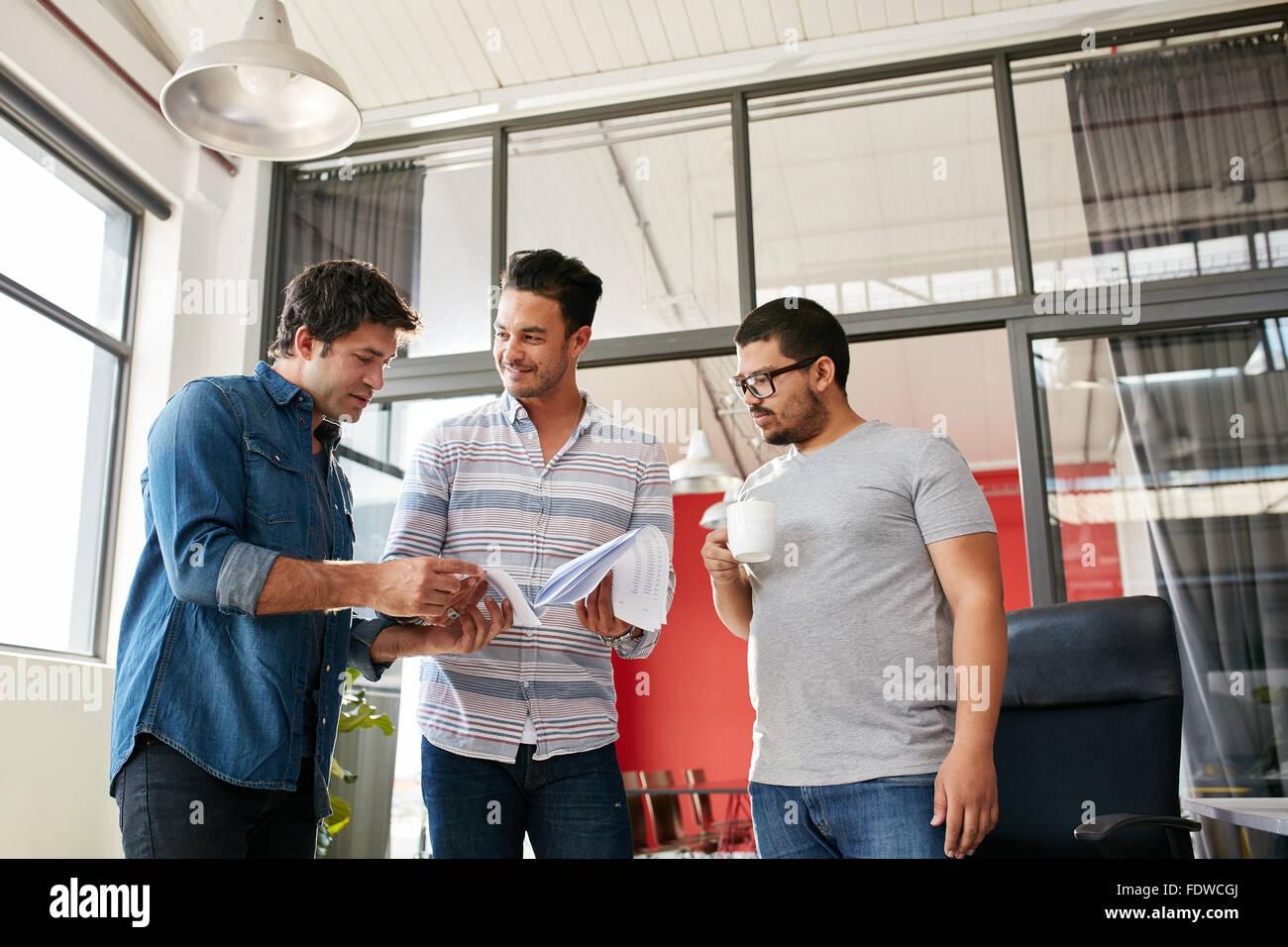 Junges Team von kreativen Menschen diskutieren Papierkram im Büro. Drei junge Männer, die im modernen Stockbild