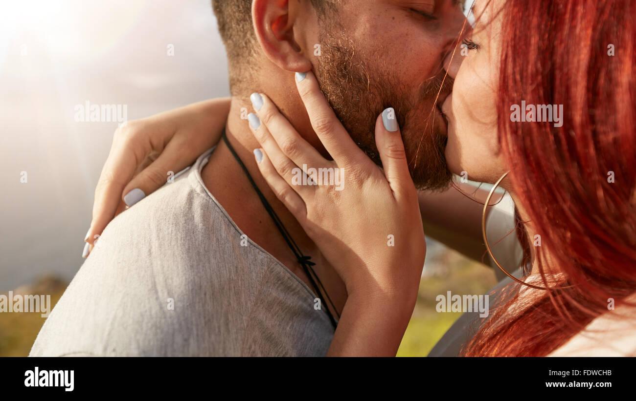 Schuss von liebevollen jungen Paar küssen im freien hautnah. Mann und Frau küssen einander romantisch Stockbild