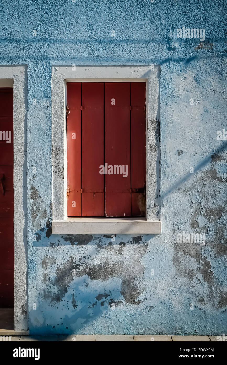 Ein aus Holz rot lackiert shuttered Fenster auf der Insel Burano in der Nähe von Venedig, Italien Stockfoto