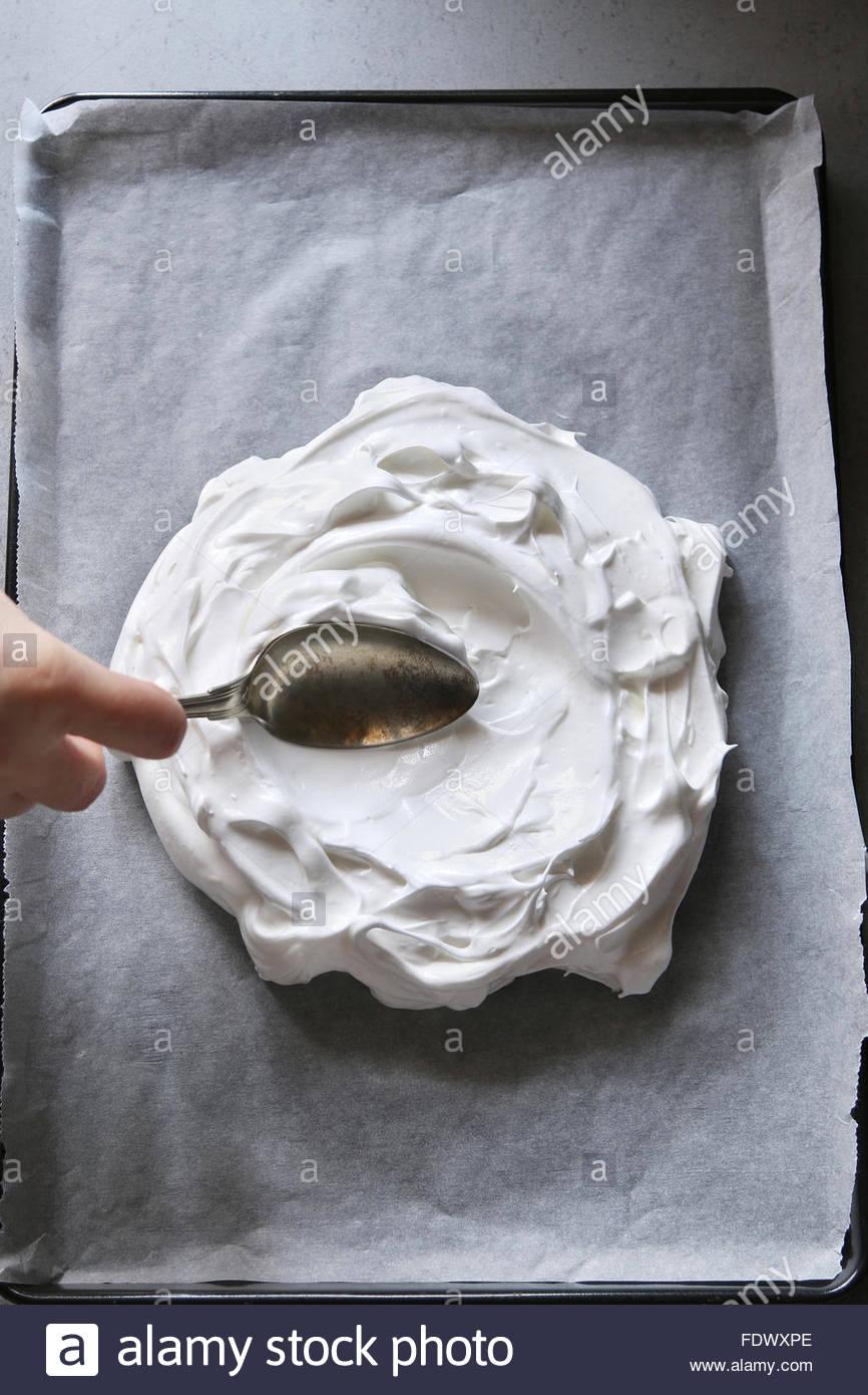Pavlova vor dem Backen auf ein Blech mit Backpapier ausgekleidet. Ansicht von oben. Stockbild