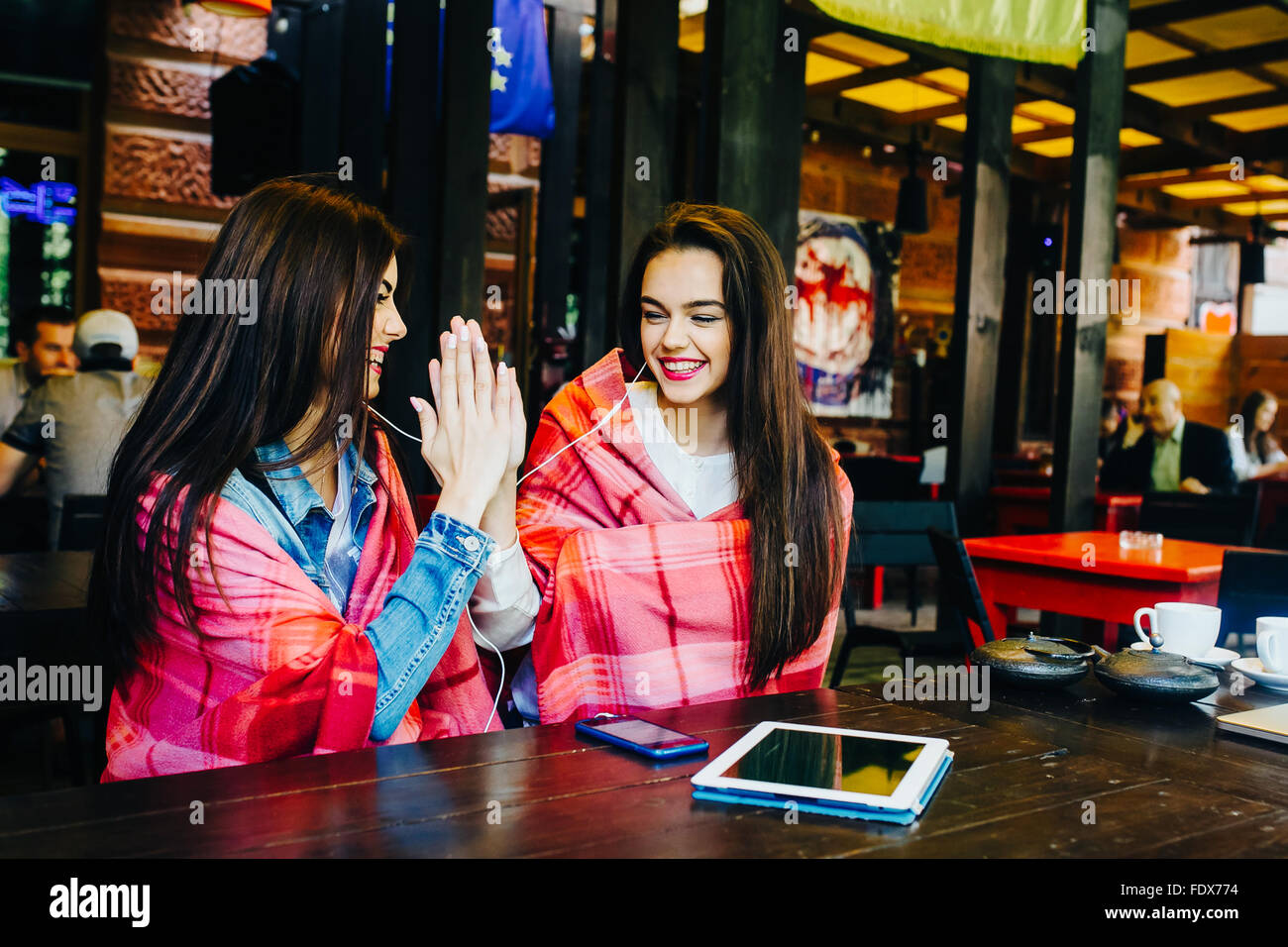 Zwei junge und schöne Mädchen, die Spaß im café Stockbild