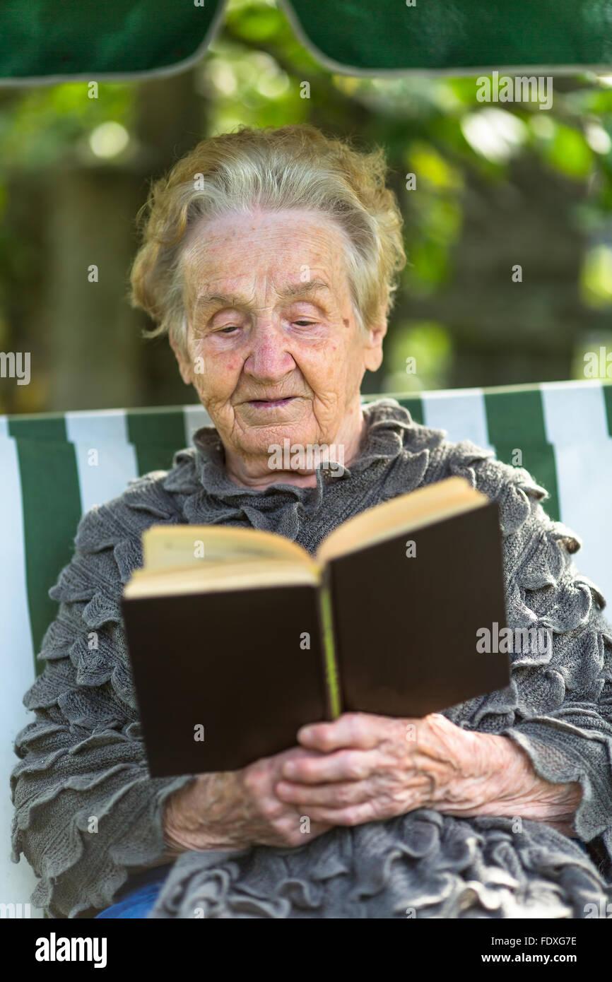 Eine ältere Frau liest das Buch in der Laube sitzen. Stockbild