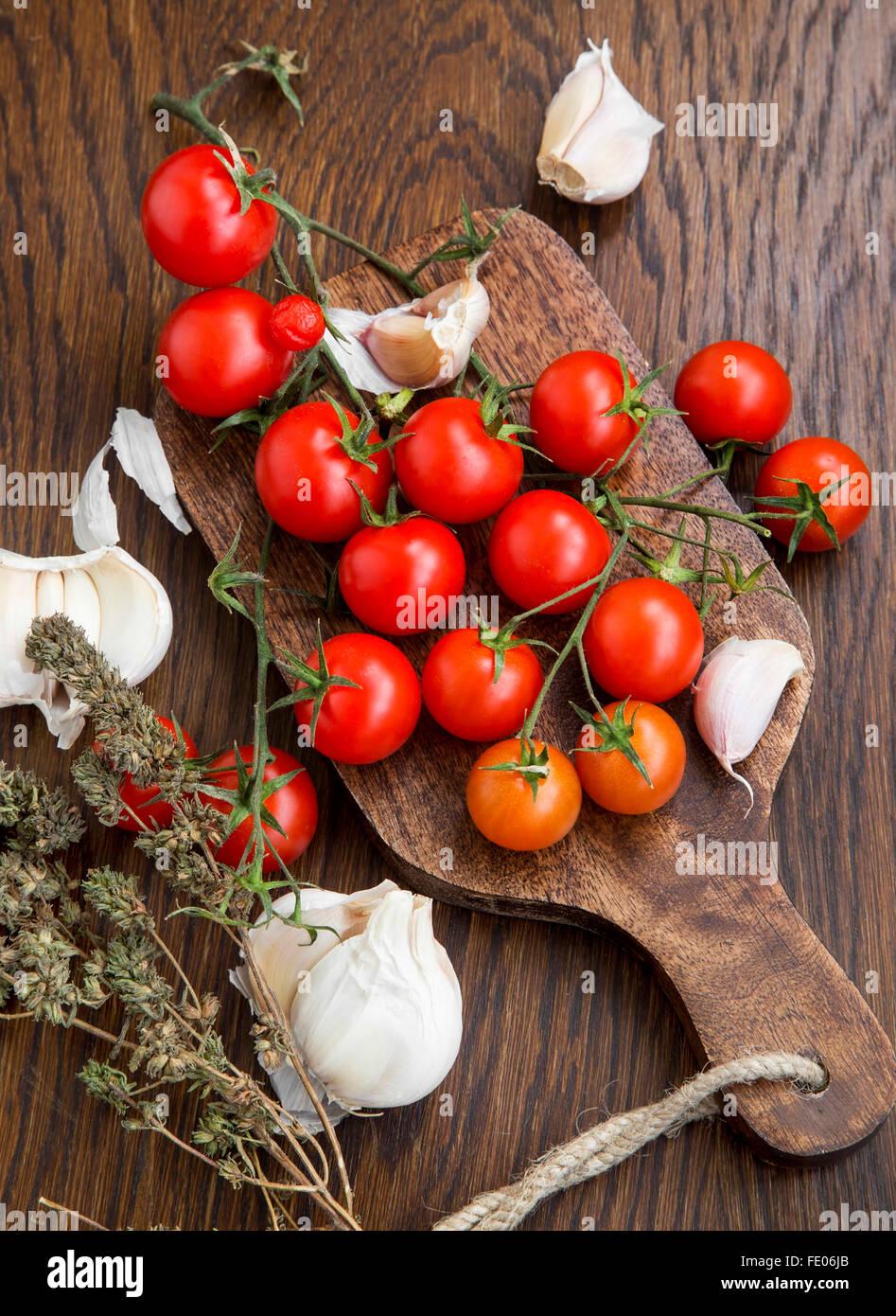 Bio Cherry-Tomaten mit Knoblauch und Thymian-Kraut auf einem Holztisch Stockbild