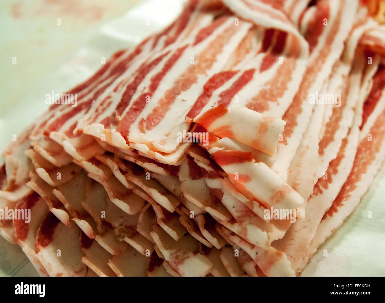 Nahaufnahme von vielen Scheiben Speck in Bündel auf Tisch in Fleischverarbeitungsbetrieb Stockbild