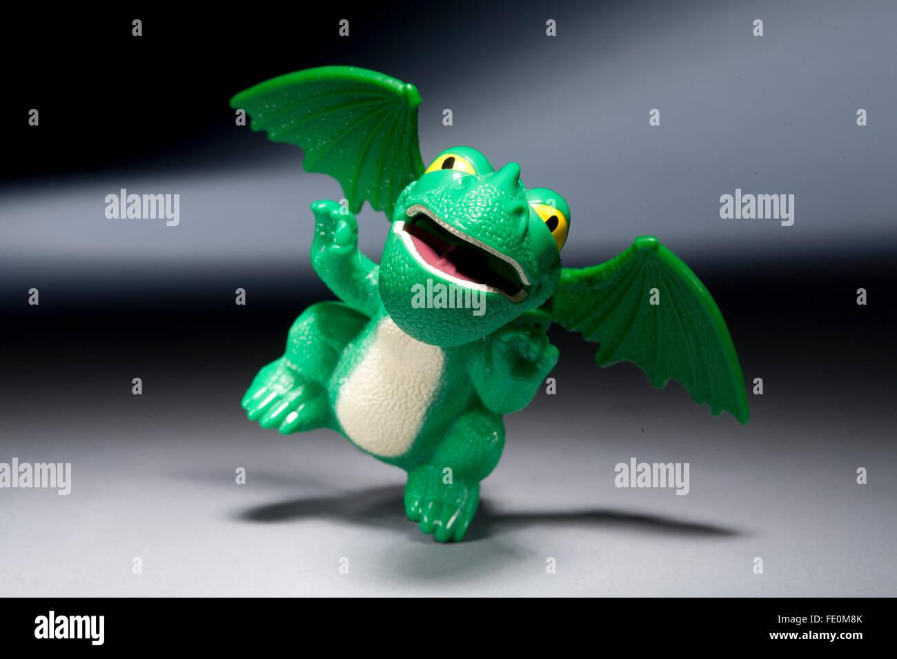 Wie Sie Ihren Drachen glücklich Essen Spielzeug auf grauem Hintergrund zu zähmen Stockbild