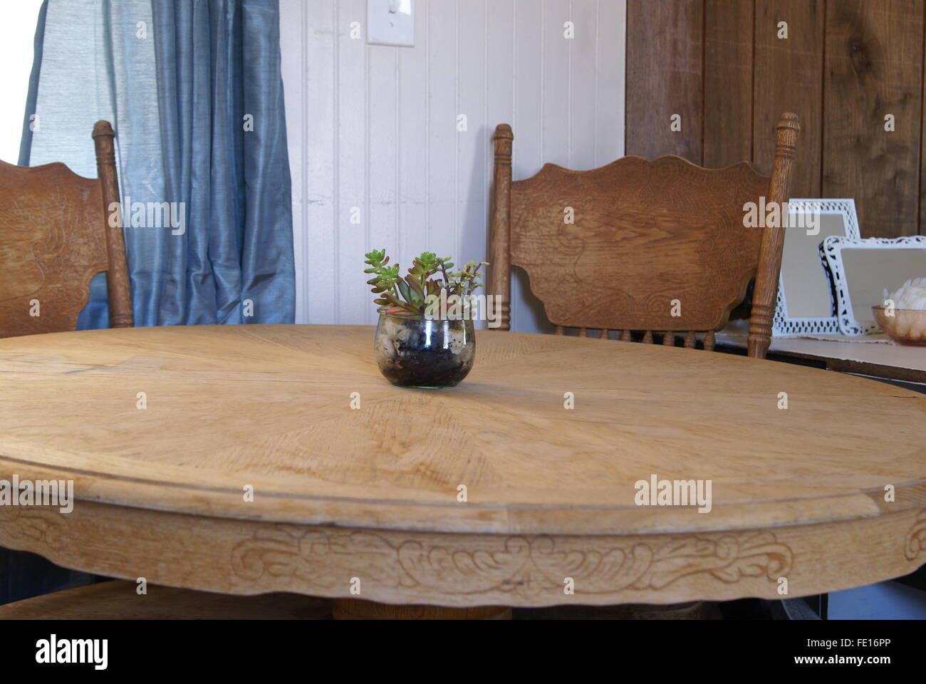 Rundes Holz Küchentisch mit eine kleine Topfpflanze in der Mitte ...
