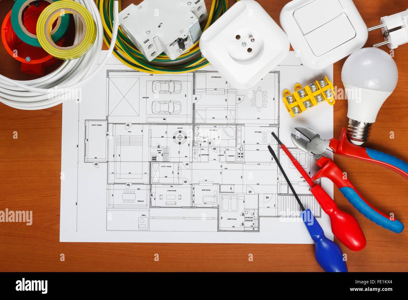Elektrische Geräte, Werkzeuge und Hauspläne auf dem Schreibtisch Stockbild