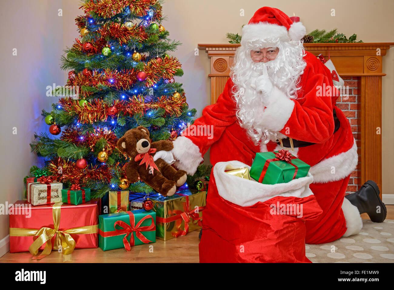 Santa Claus oder der Weihnachtsmann die Geschenke unter dem Baum während jeder schläft. Stockbild