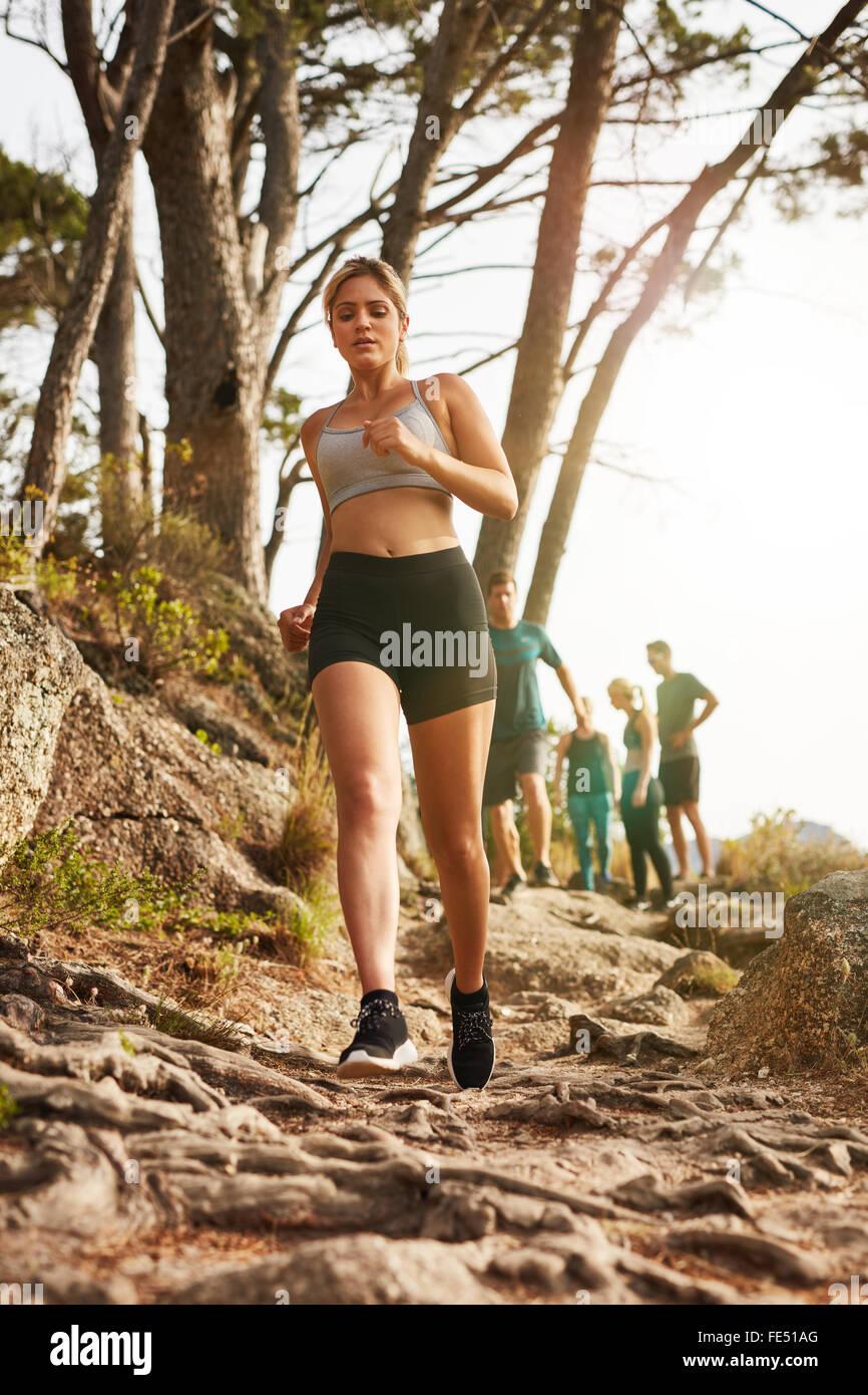 Foto von Fit junge Frau, die im freien laufen. Frau Trailläufer training für Langlauf mit Menschen im Stockbild