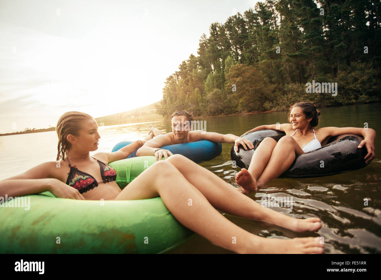 Porträt der jungen Freunde auf See mit aufblasbaren Ringen. Junge Menschen entspannen im Wasser an einem Sommertag. Stockbild