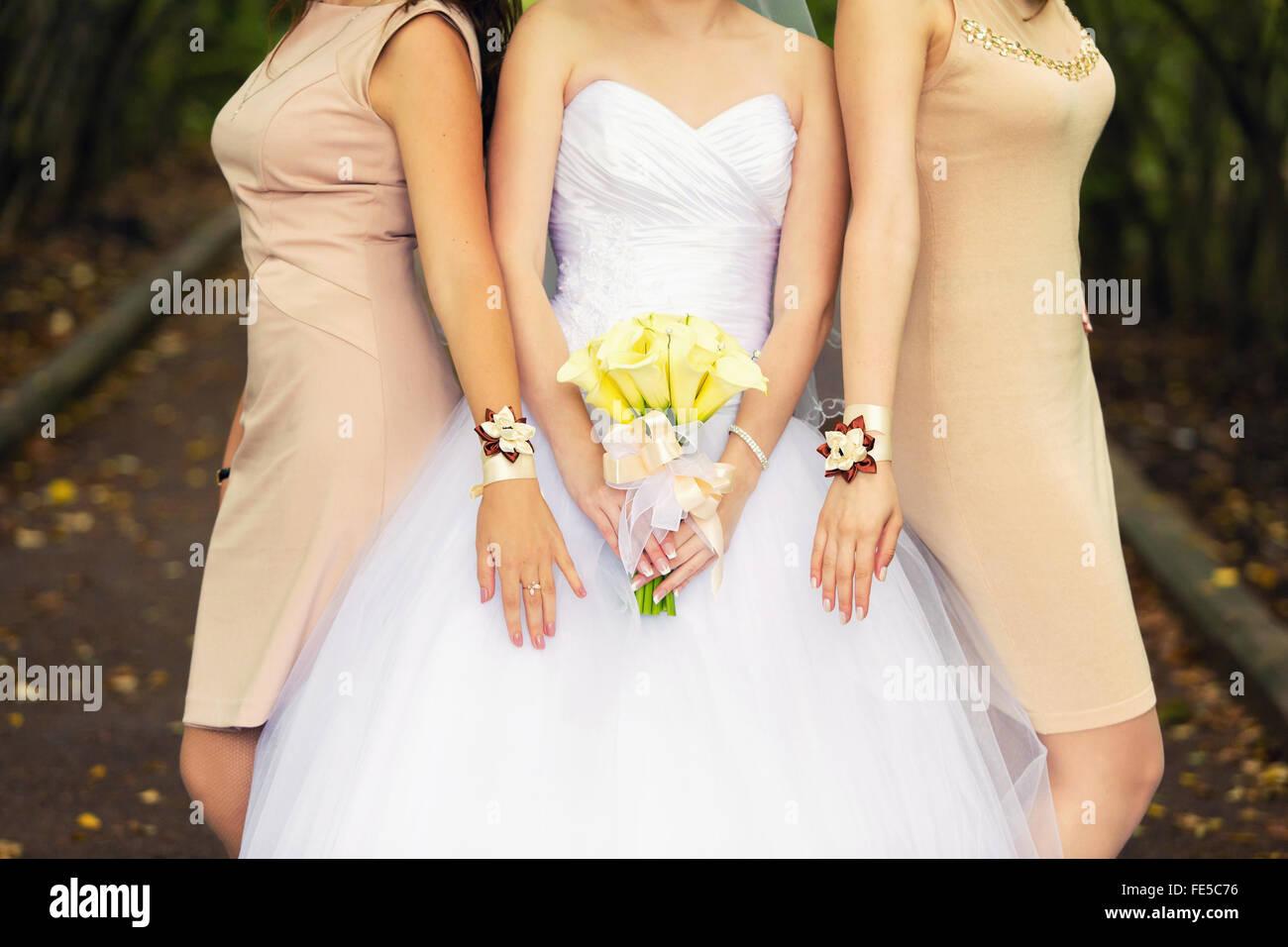 Braut mit einem Bouquet von gelben Callas und Brautjungfern in Beige ...