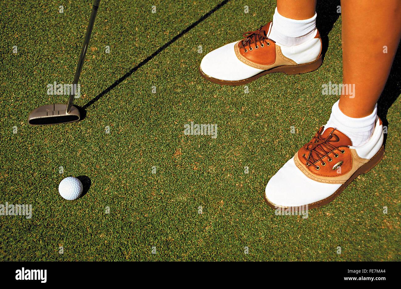Weibliche Golfer mit Schuhen, Kugel und Club auf grün Stockbild