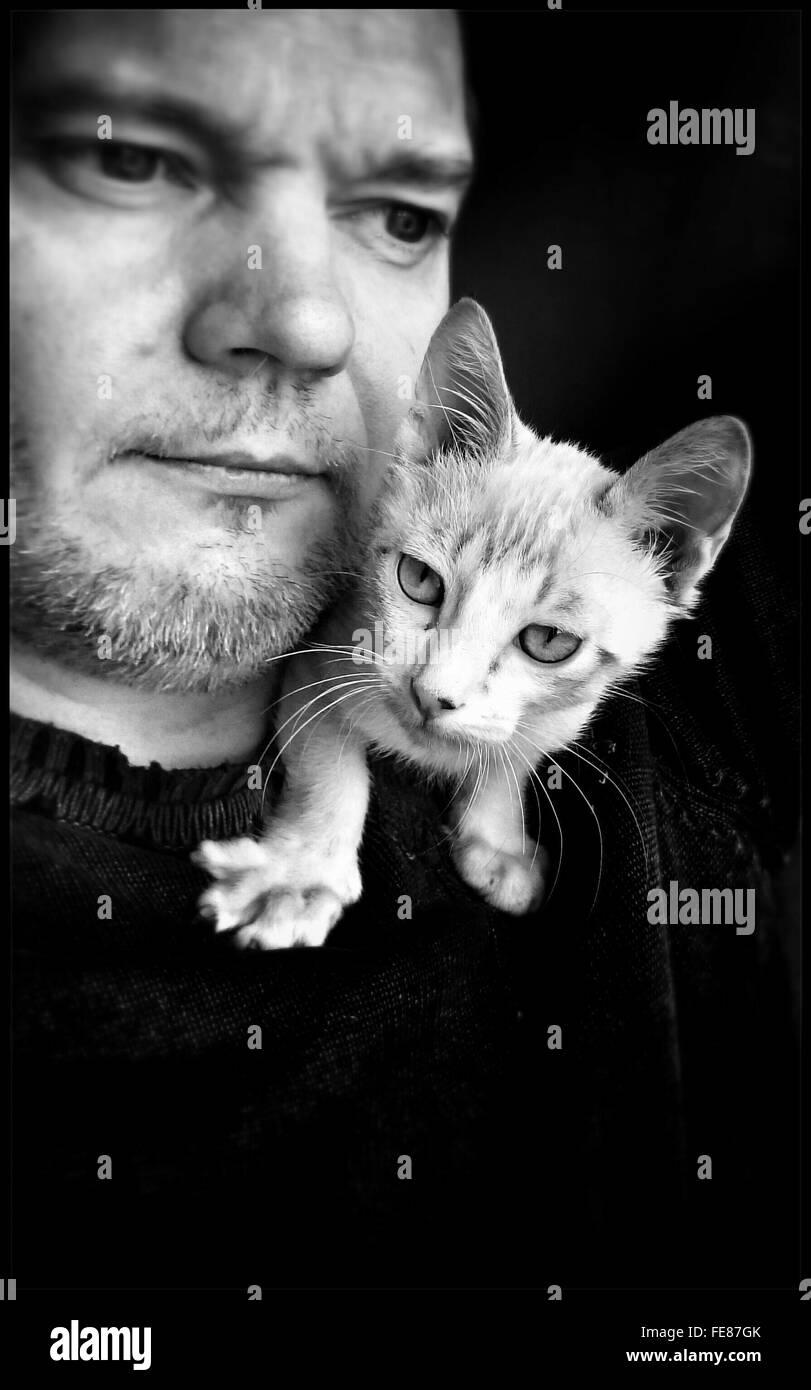 Mann mit weißen Katze auf der Schulter Stockbild
