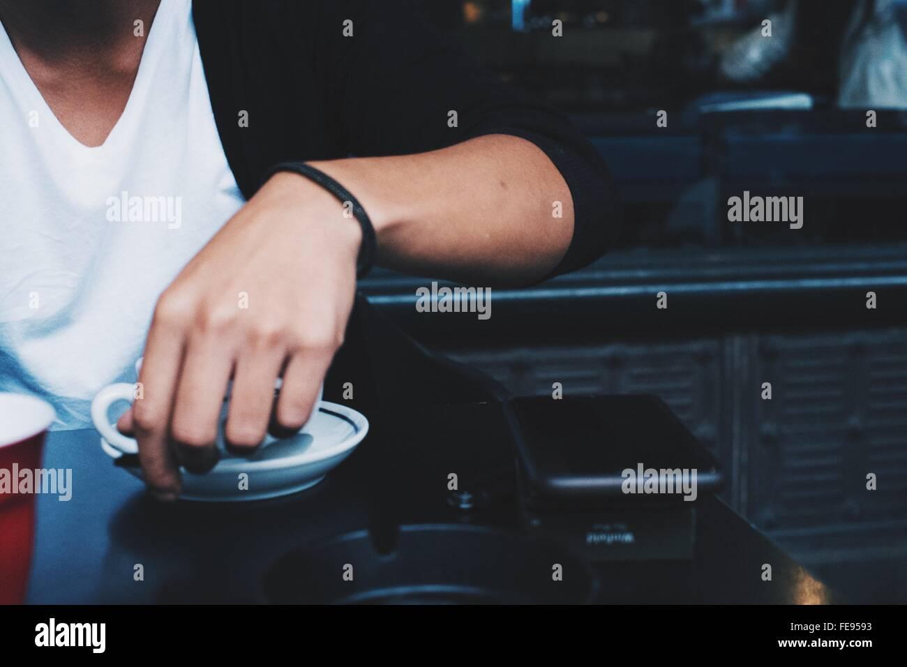 Mittelteil des Mannes Kaffeetrinken im Restaurant Stockbild