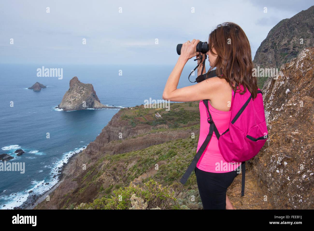 Wanderer frau oben auf dem berg blick durch ein fernglas stockfoto